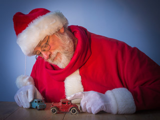 Happy Santa Claus plays with toys in the bright light
