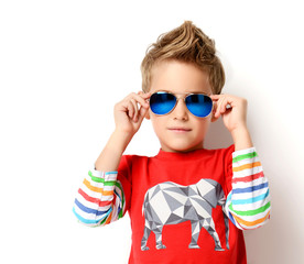 Happy young boy standing in light red shirt looking at the corner in sunglasses