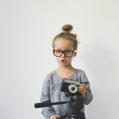 concept of a children's hobby. little girl with a camera.