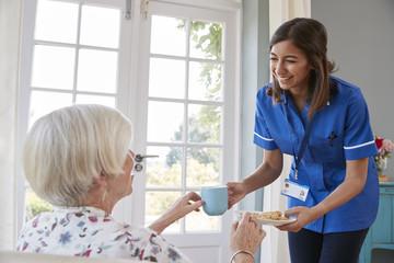 Nurse serving tea to senior woman at home, close up