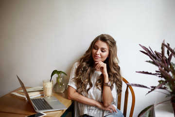 Indoor picture of playful glamourous young Caucasian female blogger or columnist sitting at table in front of open laptop, having mysterious look while thinking over new content for her blog