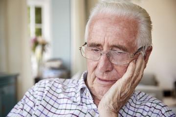 Worried senior man contemplating at home, close up