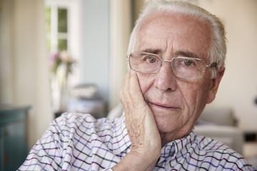 Worried senior man at home looking to camera, close up