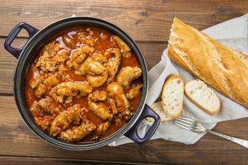 Cacerola con manitas de cochinillo, carne de cerdo en salsa y pan para un delicioso aperitivo o comida