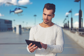 Young man ordering helicopter tour by tablet