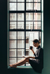 Young woman sitting by window and reading book