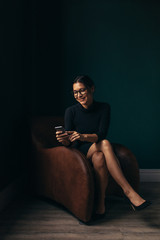 Smiling woman sitting in armchair and looking at smartphone