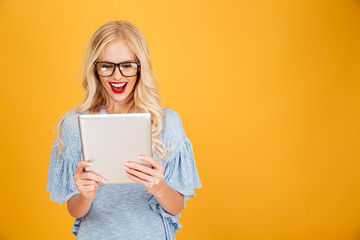 Happy young blonde woman using tablet computer.