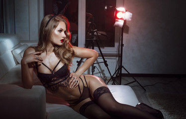 Sexy model dressed in costume Easter bunny, standing in dark room and sensually posing in black seductive lingerie