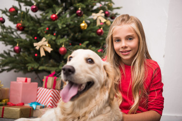 child with dog at christmastime