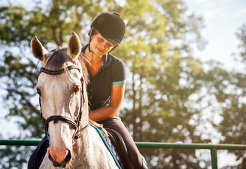 Poster Horseback riding Woman riding a horse on paddock, horsewoman sport wear