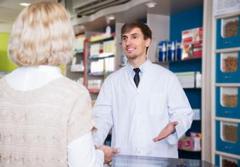 Male pharmacist talking to customer at pharmacy