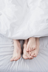 feet of couple stretching out of blanket