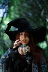 Witch in black hat with magic ball