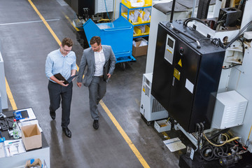 High angle view of two male managers walking and talking in factory
