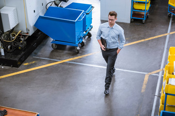 High angle view of male manager with clipboard walking in factory