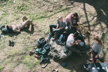 Overhead view of adult bouldering friends relaxing on grass, Lombardy, Italy