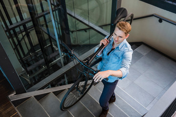 Mid adult man carrying bicycle up stairway
