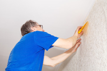 worker in protective gloves with spatula smoothing wallpaper