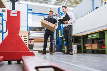 Factory manager and warehouse worker with cardboard box in warehouse