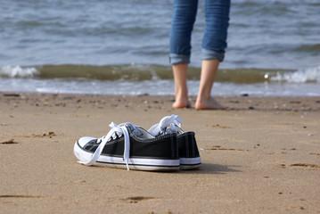 einsames Mädchen barfuß am Strand mit Turnschuhen im Vordergrund