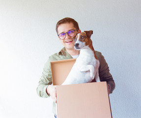 Handsome man with moving boxes and dog on white background