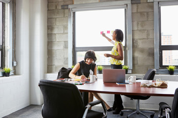 Two women working in meeting room, young woman sticking sticky notes to window