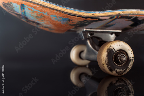 854b0b5e Partially seen skateboard on black glance background. Rubbed deck and wheels  of professional extreme sport