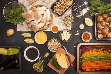 Group of raw ingredients for preparing vegetarian dinner.Oyster mushrooms, champignons, honey mushrooms, tagliatelle, cheese, quail eggs, arugula, black sesame, lemon. Healthy food concept
