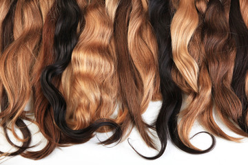 Mix of natural extensions hair: blond, red, brown. Strands of hair for hairstyles. Isolated on white background.