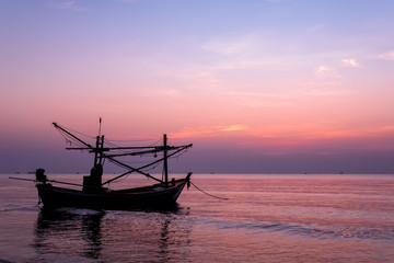 Sunrise on the sea beach with fishing boat