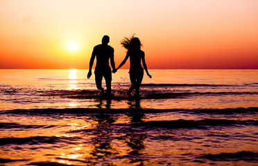 Silhouette of young fitness couple walking inside the water at sunrise - Multi race people having fun on vacation - Romantic and love concept - Soft focus on man - Sun color tones filter