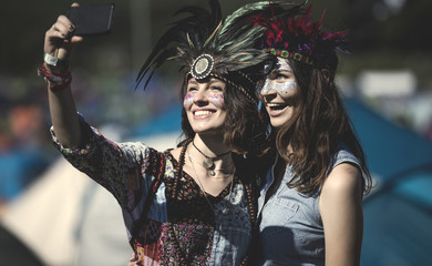 Two young women at a summer music festival faces painted, wearing feather headdress, taking selfie with smartphone.