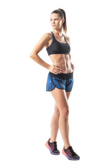 Side view of confident tough athletic woman posing and looking back over shoulder. Full body length portrait isolated on white studio background.