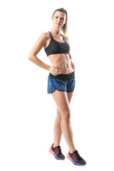 Gorgeous confident athletic fitness woman with perfect abs posing with hands on hips. Full body length portrait isolated on white studio background.