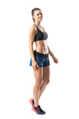 Side view of relaxed young fitness woman walking and looking at camera. Full body length portrait isolated on white studio background.