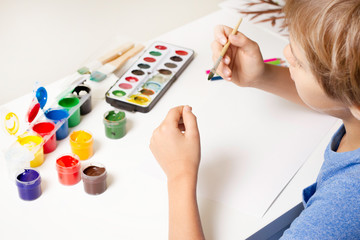 Boy painting with paintbrush and colorful gouache and watercolor paints.