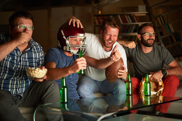 Four friends watching american football game on television