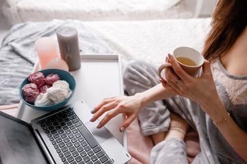 Unrecognizable young woman chatting on laptop in the morning. Early breakfast with cup of tea and zephyrs combining with social life and working, close up
