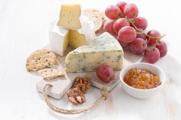 molded cheeses, fruit and snacks on a white wooden board