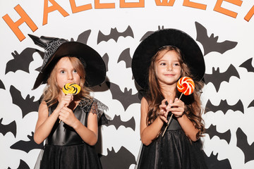 Couple of two cute little girls dressed in halloween costumes Wall mural
