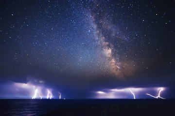 Thunderstorm on sea and milky way night sky