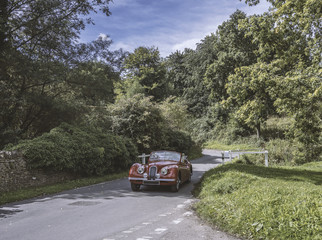Vintage Car Driving Down Country Road
