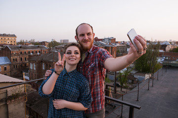 Romantic couple selfie. Modern technology. Young happy people taking picture on roof, joyful leisure time, stylish youth outdoors, fun concept