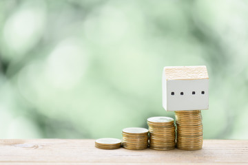 Saving money for house,stack coins and house model on wood table with pastel blurred background