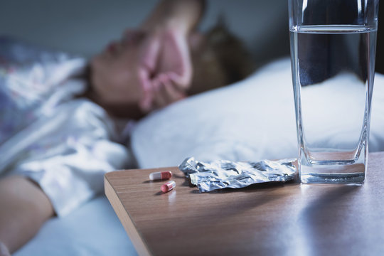 Sick woman takes capsule pill and drink water before sleeping for rest.