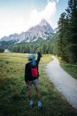 Young urban adventurer with small light backpack stands on path of beginning of hiking trail and makes photo of amazing epic mountain peak in middle of forest