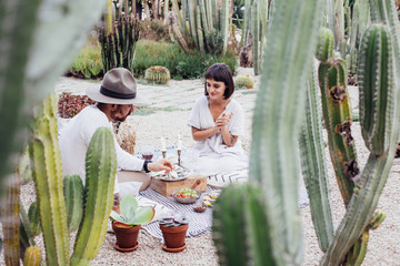 Chic trendy couple of young hipster lovers enjoy day out on romantic date, setup in summer park, enjoying wine and delicious treats and snacks, relationship goals