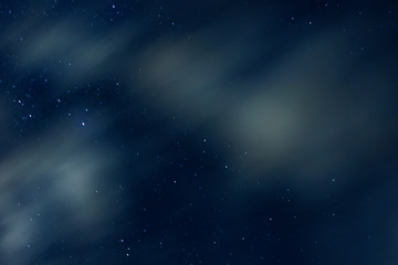 Night sky with stars and clouds in motion