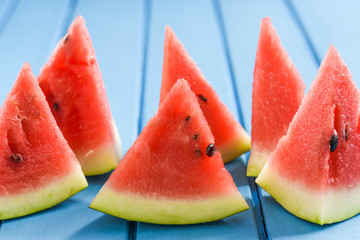 Fresh watermelon slices on blue background look like sails in sea
